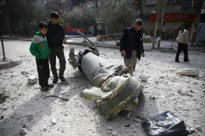 People inspect missile remains in the besieged town of Douma, in eastern Ghouta, in Damascus